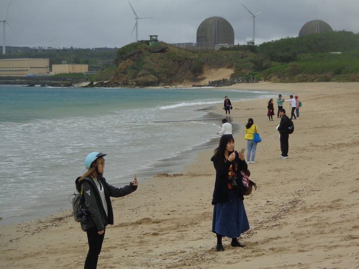 南台灣墾丁今天白天約攝氏20度,給人秋天的紓爽感覺,著大衣的遊客在南灣沙灘拍照。記者潘欣中/攝影