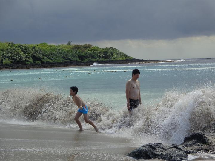 遊客換上泳衣在墾丁小灣沙灘戲水。記者潘欣中/攝影