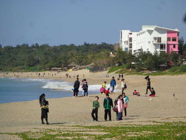 屏東墾丁上午太陽露臉,天氣回暖,遊客下到大灣沙灘享受暖暖的冬陽。記者潘欣中/攝影