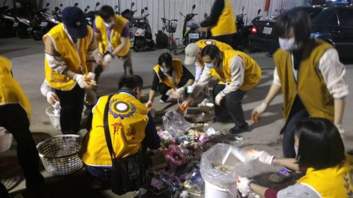 一貫道鄉親協助將垃圾分類,他們蹲在地上,將塑膠碗筷分類,救災不忘注意環保。記者黃宣翰/攝影
