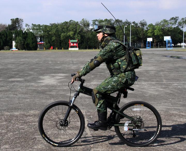 通訊兵騎乘姿態。傘兵越野折疊自行車作戰騎乘構型之通訊兵著裝,士兵背負37C無線電機配合步槍的騎乘姿態。記者洪哲政/攝影