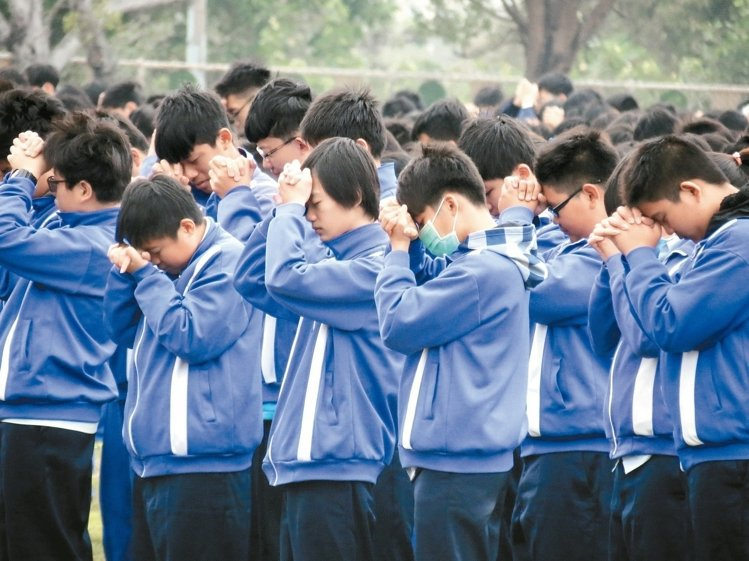 台南永康大灣高中五名學生罹難,上午開學典禮時學生低頭哀悼去世的同學。 記者周宗禎/攝影