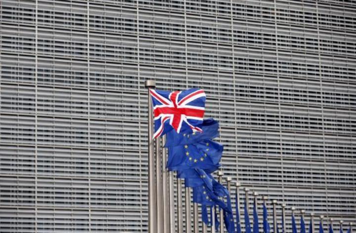 在歐盟旗幟旁迎風飄揚的英國國旗。路透