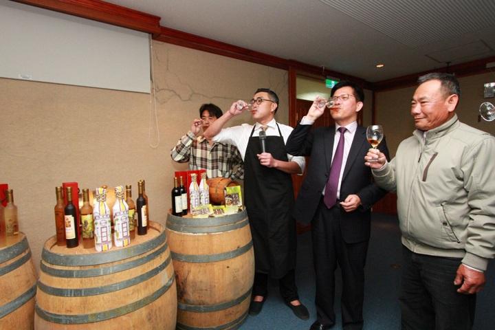 市長林佳龍(右二)、高雄餐旅教授陳千浩(左二)與樹生酒莊負責人一口喝乾金牌酒。記者陳秋雲/攝影