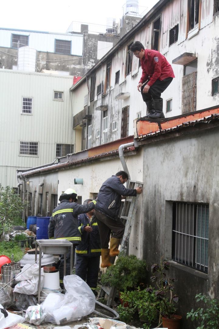 消防隊員爬上屋後勘查救火。記者謝進盛/攝影