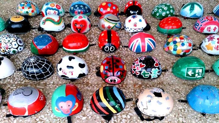 澎湖七美國中學生幫機車出租業者免費彩繪安全帽,當成另類美術教學,學生創意十足,畫出瓢蟲、櫻花、逃 生門、蜘蛛網、小雞破蛋等造型,讓業者大為驚豔。圖/七美國中提供