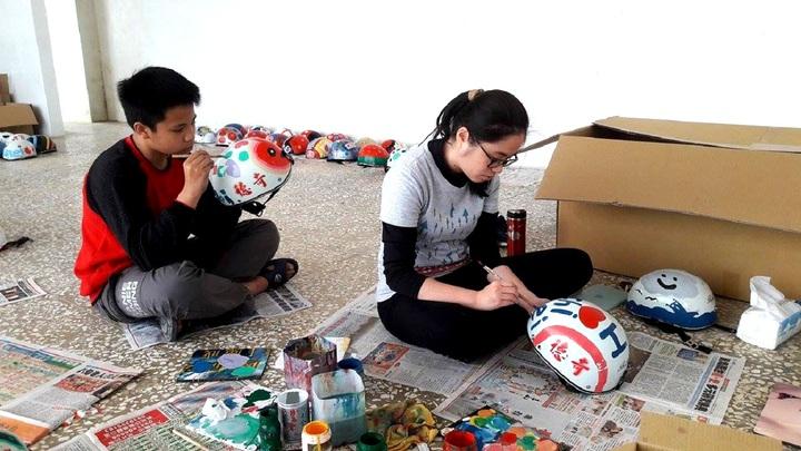 七美國中新聘的美術老師鍾佳妤(右),帶領學生用油漆彩繪安全帽。圖/七美國中提供
