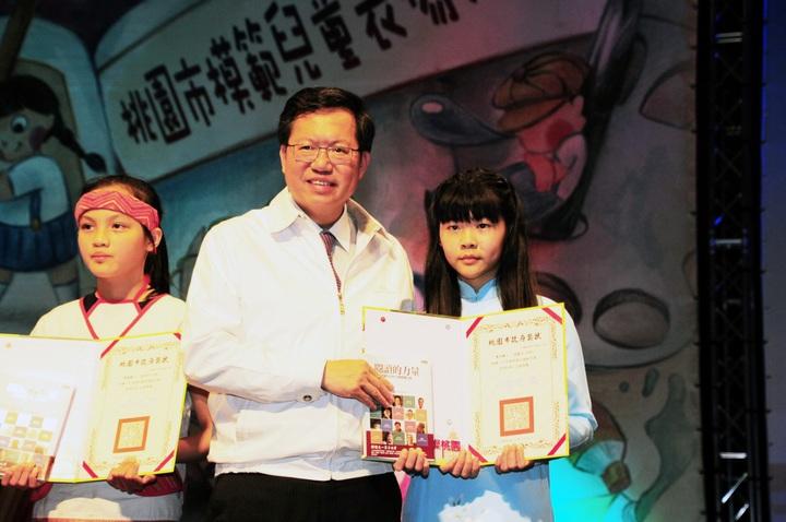 新住民二代學生(右)今年暑假要回越南,她說要和外婆分享模範兒童殊榮,市長鄭文燦(中)一一頒獎模範兒童、合照,霞雲國小學生(左)歡迎大家下復興區賞美景。記者鄭國樑/攝影