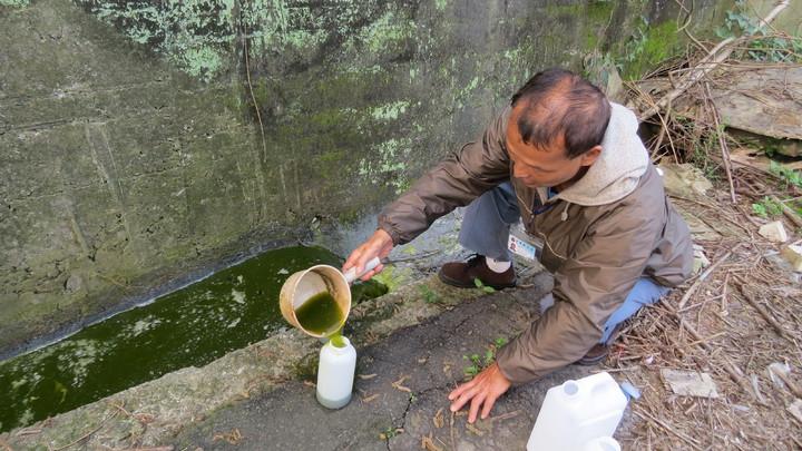 環保人員在火場周邊採取水樣,初步測得酸鹼度4,將進一步檢驗是否含毒。記者范榮達/攝影