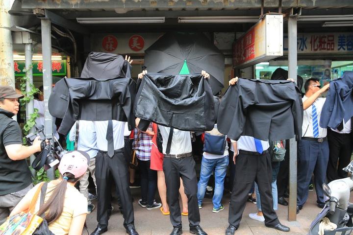 保鑣脫下西裝外套,遮擋民眾與媒體拍攝。記者林伯東/攝影