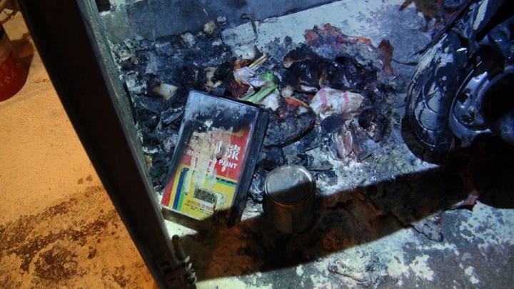 公寓鐵門內的垃圾桶和堆放在旁的兩罐已使用油漆罐,燃燒情況最嚴重,疑似就是起火點。記者王長鼎/攝影