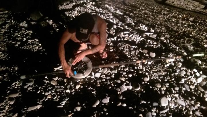 中魚斷線的釣竿倒在沙灘,陳的友人幫忙收線整理。