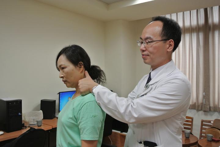 針灸科醫師馮紀新(右)替江姓婦人(左)示範「風池穴」按摩,雙手掌指尖向上貼耳,兩隻大拇指到的地方按住後腦凹陷處,輕輕按壓促進頭部循環。記者林佩均/攝影