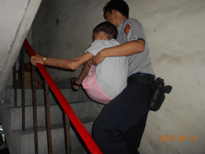警員林丞浩攙扶張婦走向公寓門口,發現老婦看著樓梯喃喃自語,想起張婦在派出所時曾提及獨居在三樓,便提議抱著她上樓,安全將她送回家。記者王宣晴/翻攝