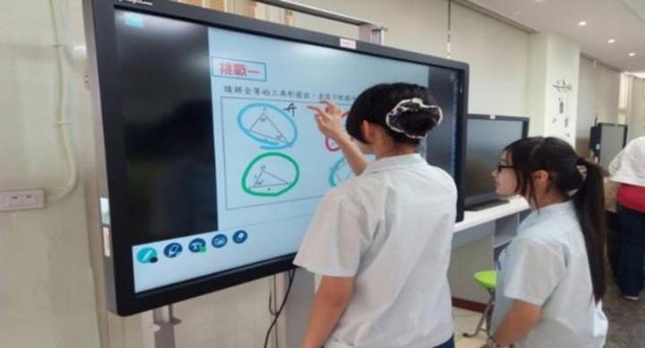 北市南門國中學生在互動式螢幕上圈選出正確的全等三角形配對及全等的種類並寫下理由,老師再將他們的答案播放給全班欣賞並討論。圖/教育部提供