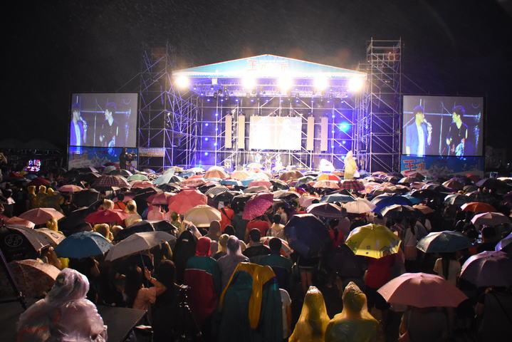 彰化縣王功漁火節今晚海洋音樂之夜,一千多名觀眾撐傘或穿著黃色輕便雨衣,耐心等待人氣偶像團體玖壹壹壓軸演出。記者何炯榮/攝影