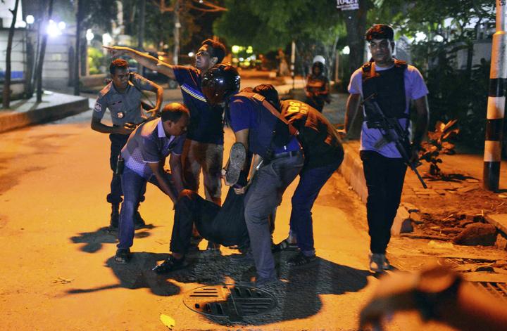 孟加拉首都達卡的餐廳遭遇恐攻,當地人一日把傷者抬出送醫。(美聯社)