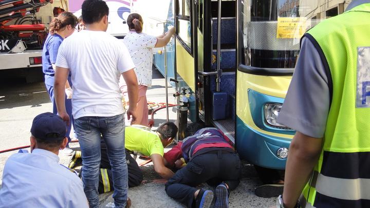 警消試圖將受困車底的女騎士救出。記者蔣繼平/攝影