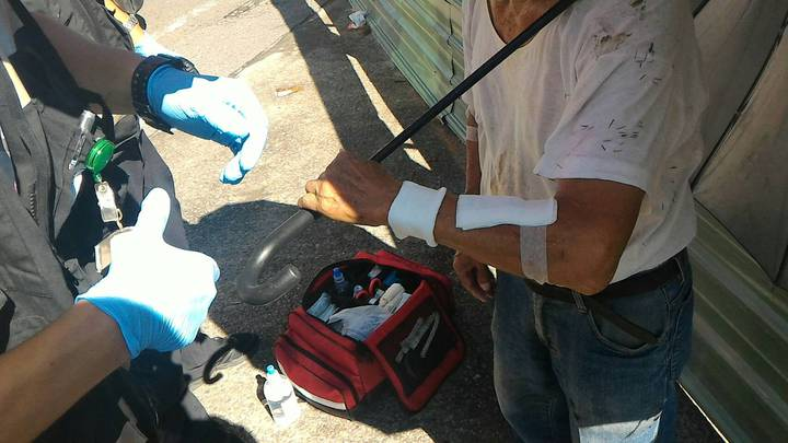 老翁疑天熱暈眩摔落田裡,警方發現後找來救護人員幫他包紮擦傷。記者鄭國樑/翻攝