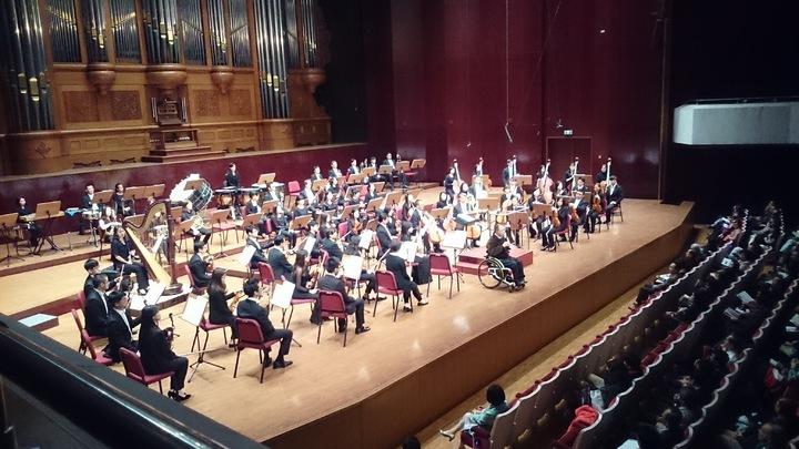 脊髓損傷基金會在國家音樂廳辦圓夢音樂會,本身也是輪椅人的董事長林進興上台向坐在最後一排的輪椅席貴賓致意,但他們有個國小女兒獨自坐在前面。 圖/脊髓損傷基金會提供