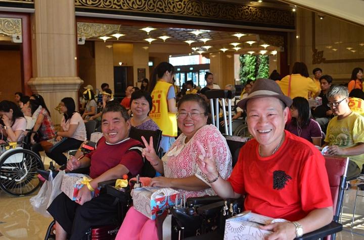 脊髓損傷基金會在國家音樂廳辦音樂會,輪椅觀眾無法進場只能聚在大廳看轉播,但因第一次來,仍開心地比「YA」手勢。 圖/脊髓損傷基金會提供