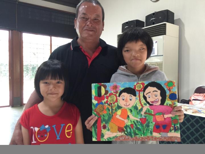 12歲的鄭惠方與爸爸、妹妹合影,手拿創作作品,名叫「愛心的照顧」。記者黃安琪/攝影