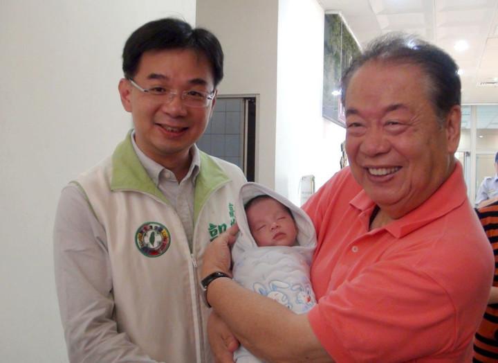 郭金發(右)生前抱孫陪同兒子郭建盟(左)登記參選高雄市議員。圖/聯合報系資料照