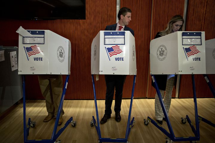 川普的兒子艾瑞克在投票所投票時,窺探自己的妻子投票。(彭博資訊)