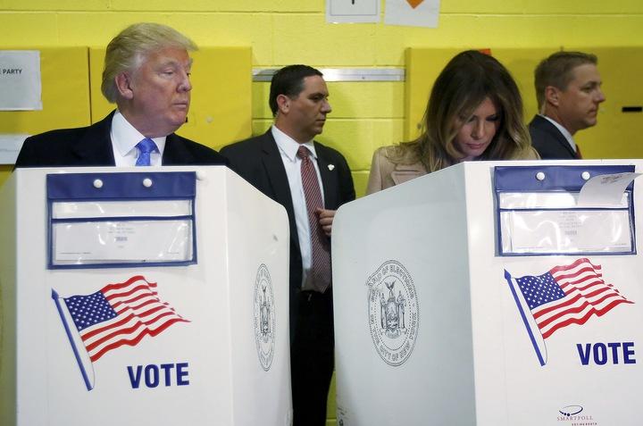川普在劃票間時,似乎窺探在一旁正在勾選選票的妻子。(路透)