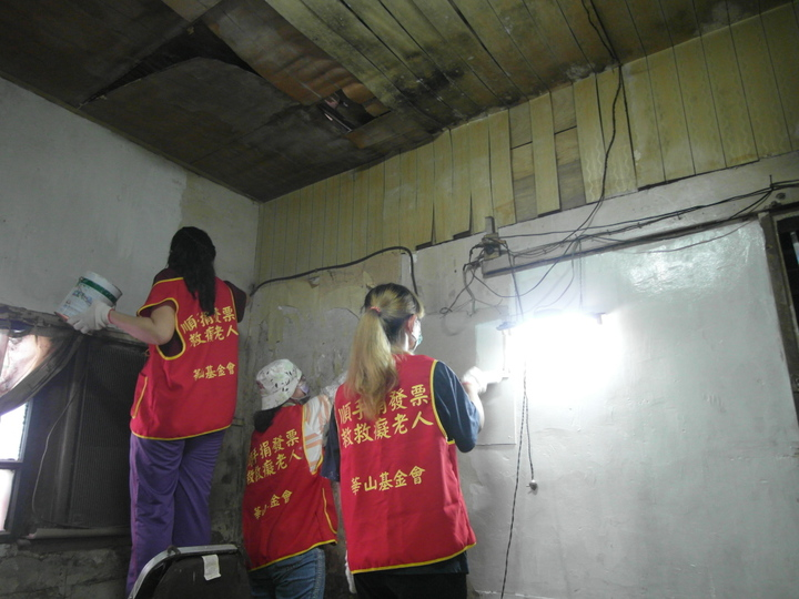 東港欣鮮魚湯的老闆娘甘真靜與華山到宅義工,協助王爺爺粉刷斑駁的牆壁和俢補塌陷天花板。記者綦守鈺/攝影