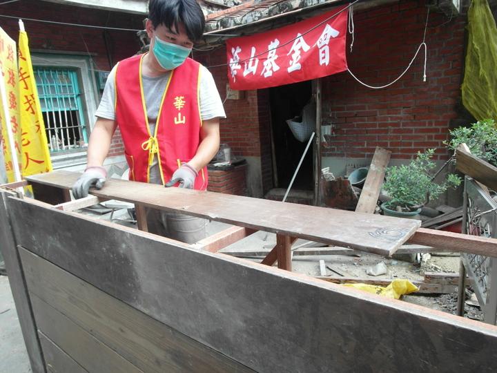 東港欣鮮魚湯的老闆娘甘真靜與華山到宅義工,協助王爺爺粉刷斑駁的牆壁和修補塌陷天花板。記者綦守鈺/攝影