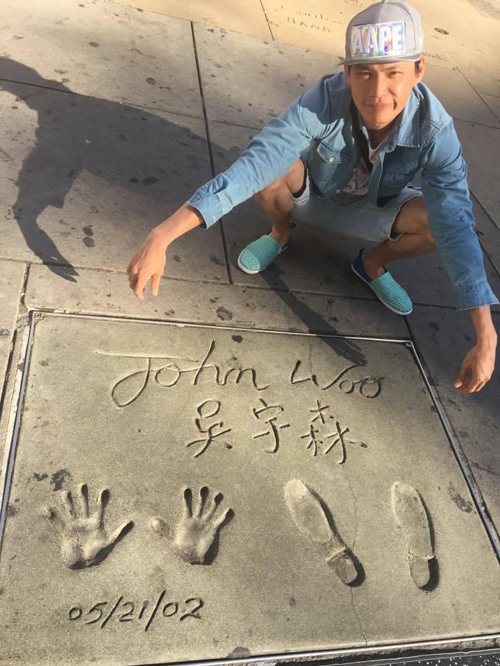 黃鐙輝在中國戲院門口跟吳宇森的手印合照。圖/黃鐙輝提供