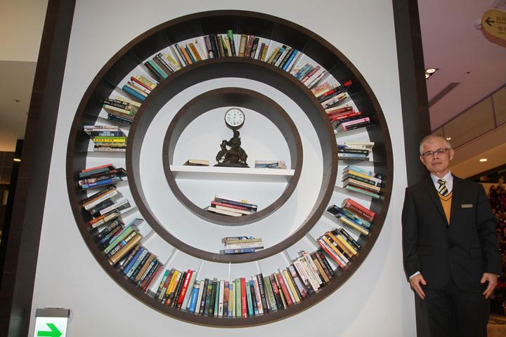 愛書的簡局能藏書萬冊,把四星級觀光飯店打造成充滿書本的房子,設計圓時鐘形的時光書櫃。記者羅建旺/攝影