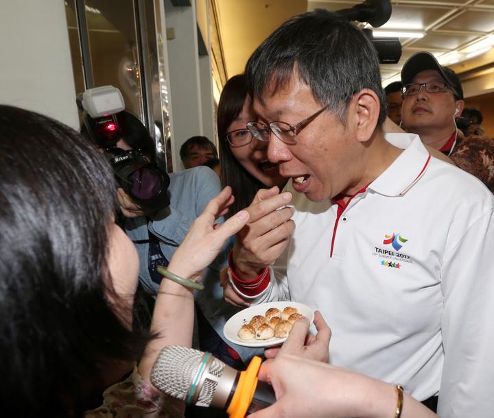 台北市長柯文哲參觀艋舺龍山文創攤位時,拿起模型餅乾直往嘴裡塞,遭工作人員及時制止。記者侯永全/攝影