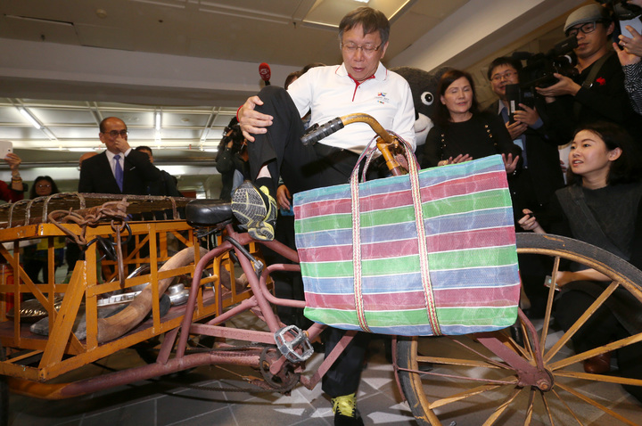 台北市長柯文哲參觀艋舺龍山文創攤位,看到古老三輪車時,抬高腿試坐,展現「柔軟身段」。記者侯永全/攝影