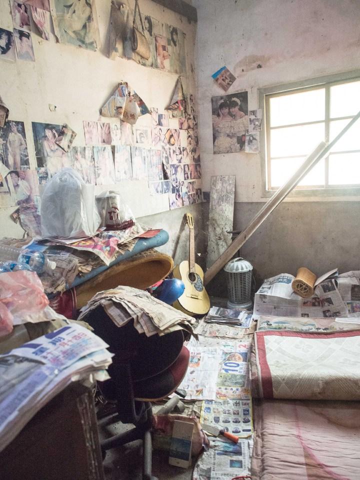 黃姓長者用在地上鋪著床墊、旁邊還用報紙吸滴下來的水。記者林良齊/攝影