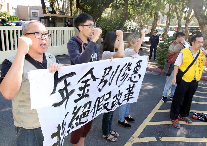 桃園市產業總工會理事長莊福凱(右一)率工會代表到行政院大門口前抗議年金改革。記者屠惠剛/攝影