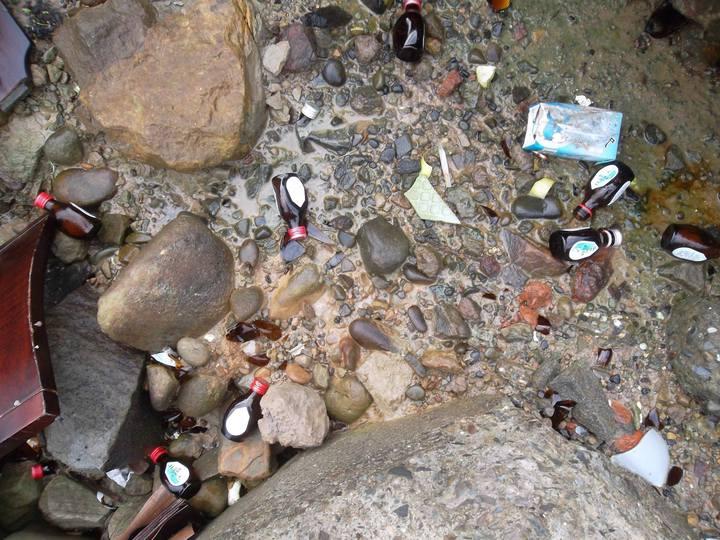 陳信助在海邊淨灘,發現整批感冒藥水瓶散落岸邊。圖/陳信助提供