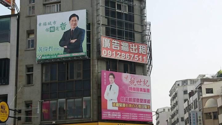 立委黃偉哲豎立在台南市東區開山路與大同路口的看板,與旁側醫美廣告形成有趣對比。記者鄭惠仁/攝影