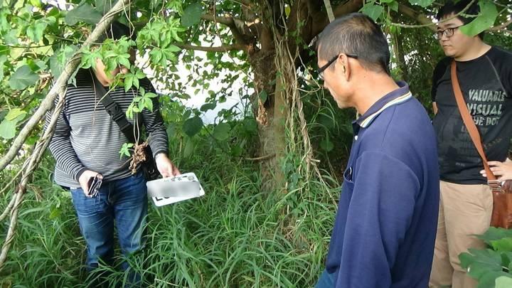 曾姓男子(右二)涉搶被捕,帶警方在草叢內找到他涉案後丟棄的機車贓牌。記者林保光/翻攝