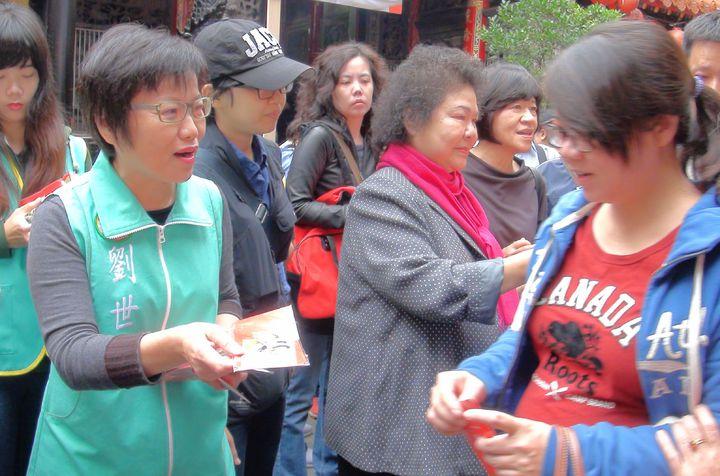 有意爭取民進黨提名的立委劉世芳(左一)今天和高雄市長陳菊(左二)到鳳山雙慈亭發送春節小紅包袋。記者楊濡嘉/攝影