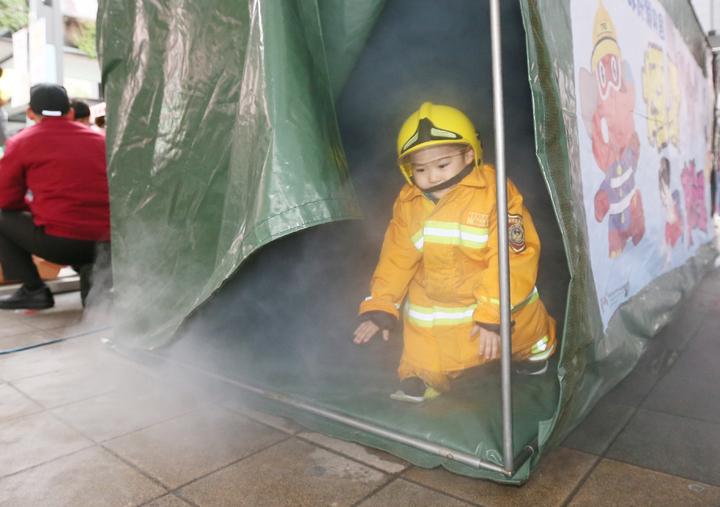 小朋友穿著消防衣,體驗在濃煙中逃生。記者許正宏/攝影