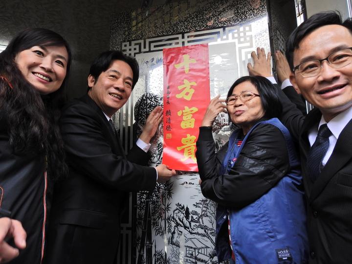 台南市長賴清德(左二)今天為台南市新市區三民街地震受災戶「入厝」,張貼「十方富貴」春聯。記者吳淑玲/攝影