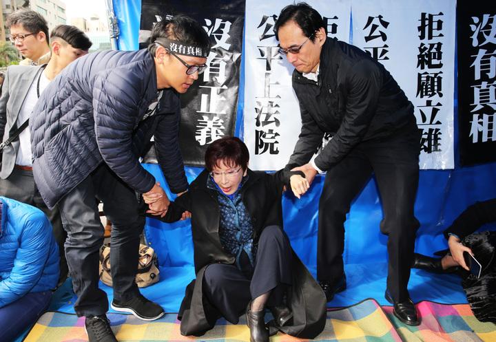洪秀柱(中)起身要離開時,國民黨秘書長莫天虎(右)及黨工一左一右扶洪秀柱站起來。記者徐兆玄/攝影