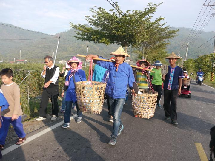 送字紙祭隊伍步行前往美濃溪,參與活動的地方人士下場體驗挑竹簍。記者徐白櫻/攝影