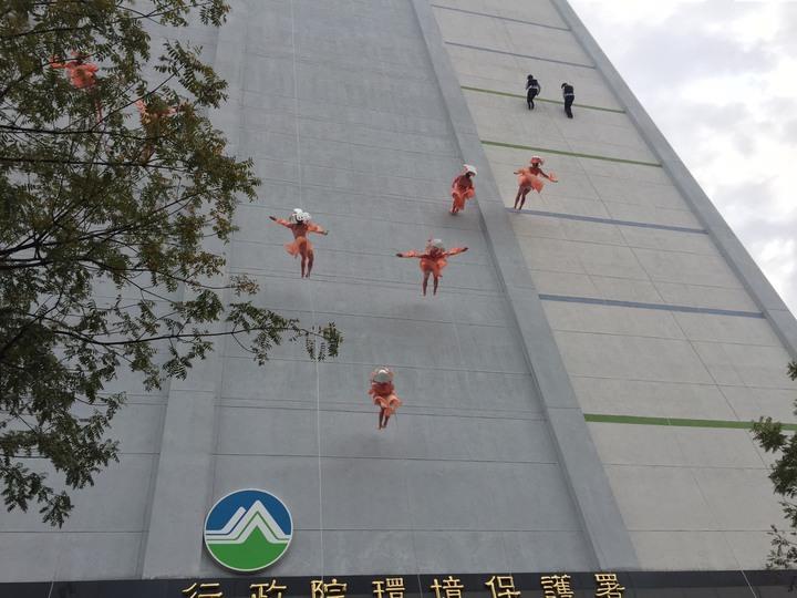11名舞者從14層樓高、40多公尺高度、吊掛繩索沿著環保署大樓牆面垂直而下,以空中舞蹈呼籲各界一起減塑。記者洪欣慈/攝影