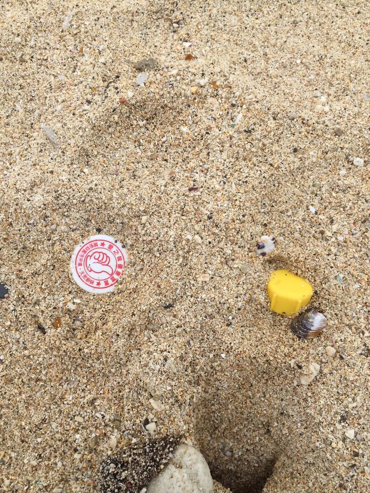 小琉球沙灘上可以在貝殼砂當中發現不少瓶蓋。記者蔣繼平/攝影