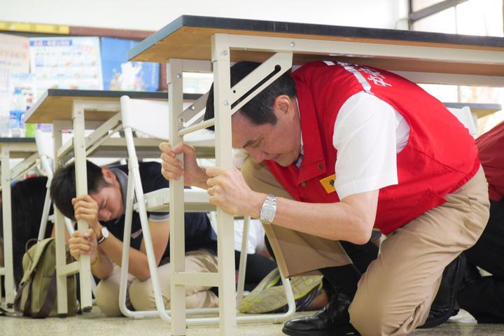 圖為前總統馬英九前年參加國家防災日地震避難掩護演練,在教室與學生進行突遇地震時躲在桌下等避難演練。圖/教育部提供