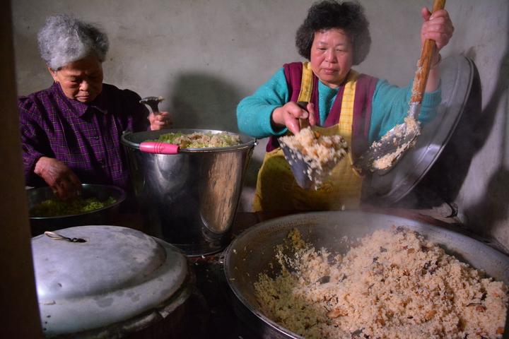 台南市新化大坑尾住戶一早就起灶煮「鹹飯」,招待遶境陣頭及遊客。記者吳淑玲/攝影