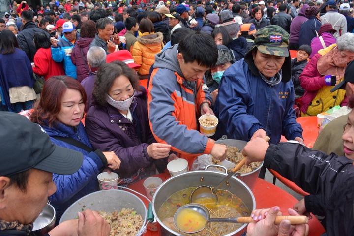 台南市新化「大坑尾擔飯擔」活動,今天有上千遊客湧入聖母宮前享用住戶準備的「飯擔」美食。記者吳淑玲/攝影
